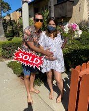 The Parizos pose for a photo after buying their first home, a two-bedroom condo in Oxnard, during the coronavirus pandemic.