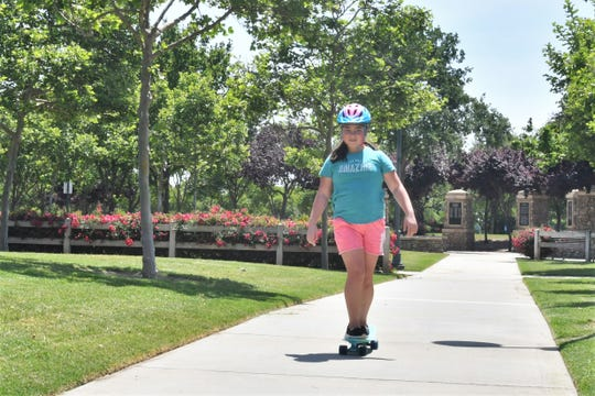 Emma Prouty rides a skateboard at Visalia's Riverway Sports Park Thursday. The city reopened park amenities this week after closing them April 3 in response to the coronavirus pandemic.