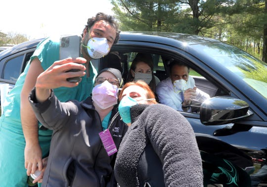 New York State Governor Andrew Cuomo stops his car to take a selfie with David Bass, Maria Clara Lorca, and Dawn Spatz, all medical staff members at Westchester Medical Center in Valhalla, N.Y. May 7, 2020. Cuomo had just finished his daily coronavirus press briefing at New York Medical College on the campus of the medical center. With Cuomo was his secretary and top aide Melissa DeRosa.