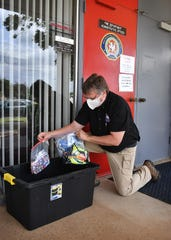 John Henderson, Wichita Falls emergency preparedness coordinator, picks up cloth face masks donated in response to a request by the city. Drop off tubs are located at each of the city's eight fire stations.