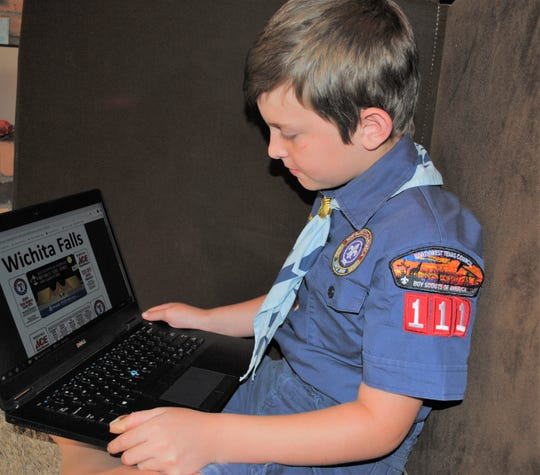 Carter Kowalick, 9, a Bear Cub Scout with Pack 111 of the Northwest Texas BSA Council, looks at the online camp cards. Every spring, fundraising sales from these cards helps Scouts like Carter go to BSA summer camp. The cards are offered for purchase online for no-contact delivery.