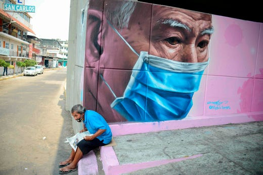 A man sits next to a mural of a man wearing a face mask in Acapulco, Mexico, on May 6, 2020, amid the new coronavirus pandemic.