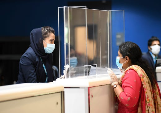 An Indian woman checks in at the Dubai International Airport before leaving the Gulf Emirate on a flight back to her country, on May 7, 2020, amid the novel coronavirus pandemic crisis. The first wave of a massive exercise to bring home hundreds of thousands of Indians stuck abroad was under way today, with two flights preparing to leave from the United Arab Emirates.