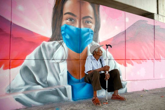 An elderly man sits behind a mural of a woman wearing a face mask in Acapulco, Mexico, on May 6, 2020, amid the new coronavirus pandemic.