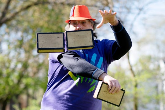 Preston Eakins juggles cigar boxes in his front yard on Friday, May 8, 2020 in Kalamazoo, Mich. Eakins is entering a virtual talent show that is taking place during the coronavirus pandemic.