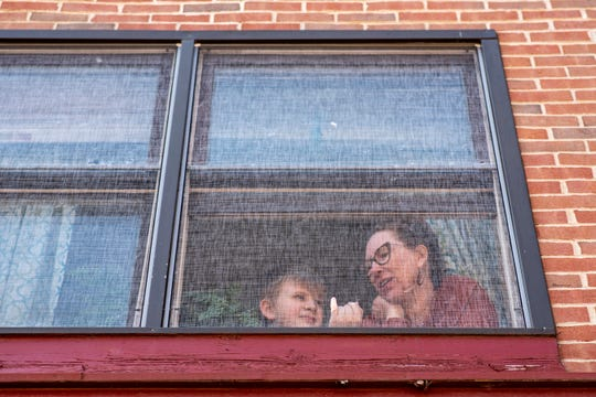 """George Pyatt, 11, sticks his finger through a window screen next to his mom Jill Anderson on Wednesday, March 25, 2020 at their apartment in Battle Creek, Mich. On Monday, Gov. Whitmer issued a """"stay home"""" order to slow the spread of COVID-19, ordering Michigan residents to stay at home except for essential purposes."""