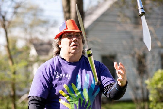 Preston Eakins juggles knives in his front yard on Friday, May 8, 2020 in Kalamazoo, Mich. Eakins is entering a virtual talent show that is taking place during the coronavirus pandemic.