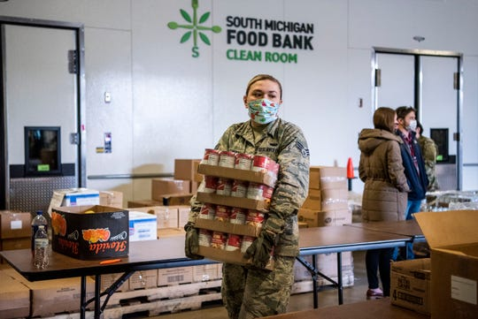 U.S. Air Force National Guard solider Eran Mikolowski packages food at South Michigan Food Bank in Battle Creek, Mich. on Tuesday, April 21, 2020 as unemployment numbers soar to record highs throughout the COVID-19 pandemic.