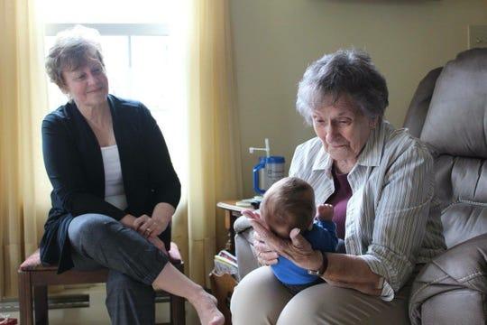 Linda Macbeth watches her mother, Helen Bennet, holding her great-grandson, Tanner.