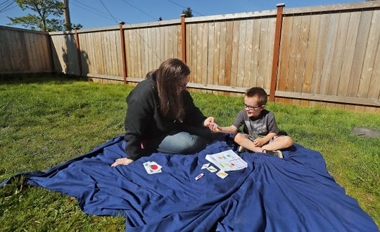 Erin LeMieux and her son Remy, 4, work through a stack of flashcards in the yard of their Bremerton home on Friday. Remy was receiving speech therapy at Armin Jahr Elementary through Head Start before schools shuttered in response to the pandemic. Parents are now in the position of working with their children on therapies for preschool and school-age children.