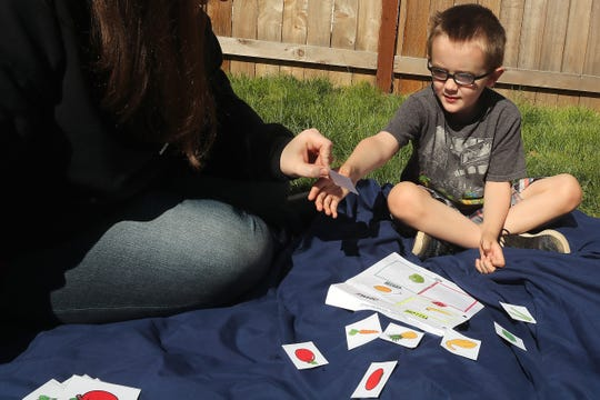 Erin LeMieux and her son Remy, 4, work through a stack of flashcards in the yard of their Bremerton home on Friday.  LeMieux and her husband work with Remy on speech therapy exercises each week as well as helping their older children, students at View Ridge Elementary in Bremerton, with their schoolwork.