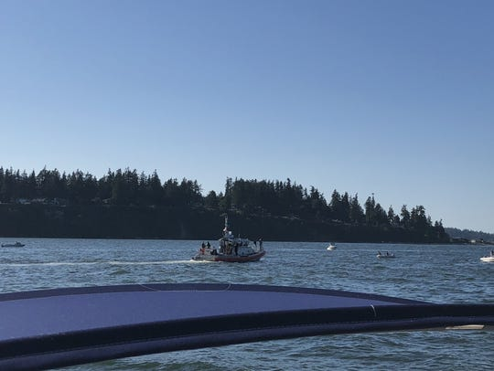 A Coast Guard boat and other vessels search the waters off Bainbridge Island for a plane that crashed there in May 2018.
