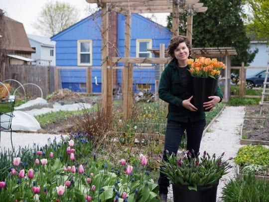 Kelsey Adams, who runs West Lane, holds tulips in her Winooski garden. May 8, 2020.