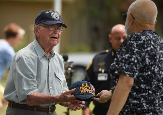 Bob Batterson receives a US navy veteran hat from a driver during his a surprise parade in his honor, Friday, May 8, 2020. Batterson is a World War II veteran and Pearl Harbor survivor.