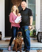 Ashley Danielson and her husband hold their daughter Veda in front of their home. This Sunday will be the couple's first Mother's Day with their daughter, and they aren't sure whether any family will be able to hold her.