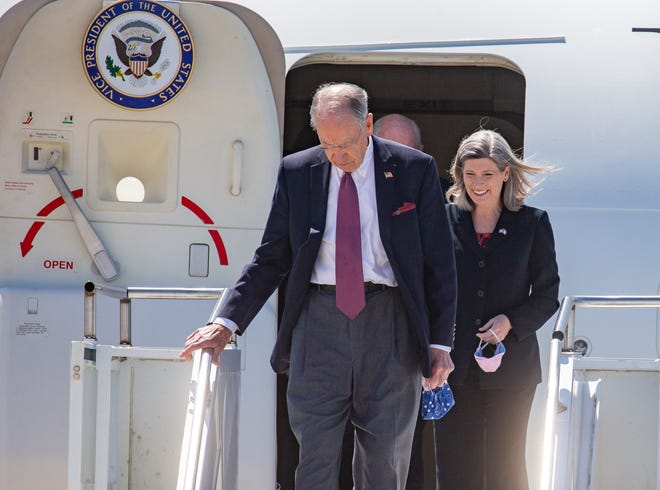 Senators Chuck Grassley, R-Iowa and Joni Ernst, R-Iowa carry masks as they arrive at the Des Moines International Airport aboard Air Force Two Friday, May 8, 2020.