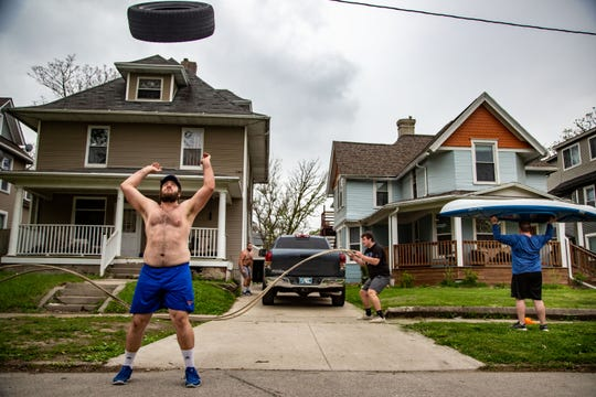 Drake University football player Zack Clark tosses a tire in the air as he and his fellow offensive linemen workout with items like a kayak, ropes, a truck, and a tire Thursday, May 7, 2020.