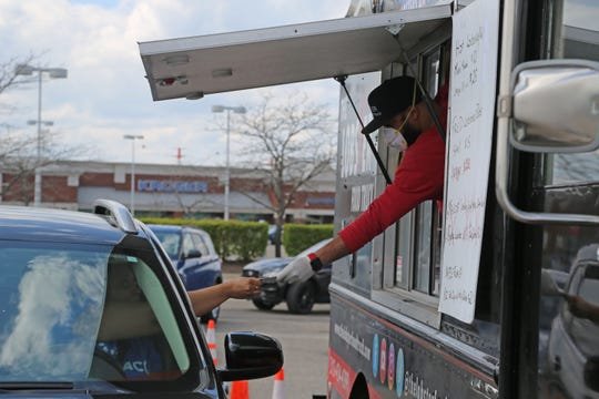 Nick Wilson, co-owner of The Lobster Food Truck, takes a customer's payment in the parking lot of the Home Depot in Troy on May 7, 2020. To survive a summer without events -- the lifeblood of food trucks -- The Lobster Truck sets up for drive-through service in parking lots across metro Detroit.