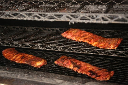 Slabs of ribs turn in the industrial smoker at the Detroit BBQ Company food truck's commisary kitchen in Ferndale on May 7, 2020. In response to a summer of canceled events due to COVID-19, Detroit BBQ Company is serving curbside carryout out of its commissary on 8 Mile.