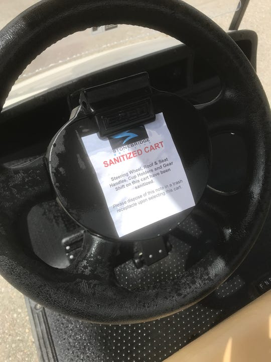 "A notice on a golf cart at Stonebridge Golf Club in Ann Arbor reads: ""Steering Wheel, Roof & Seat, Cup Holders and Gear Shift on this cart have been sanitized."""