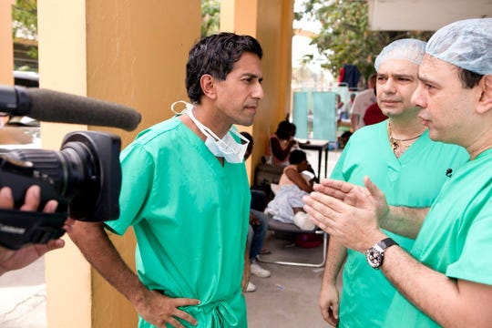 Dr. Sanjay Gupta, left, has been consumed by coronavirus coverage. He gives daily updates on CNN.