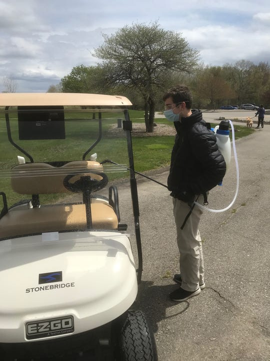 A golf course attendants sprays disinfectant on golf carts at Stonebridge Golf Club in Ann Arbor.
