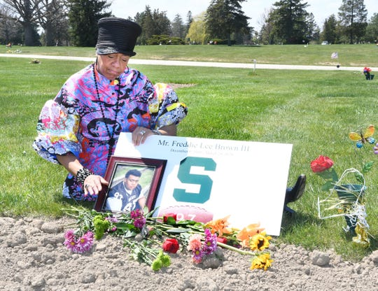 Sandy Brown of Grand Blanc places flowers on the gravesite of her only son Freddie Lee Brown III and husband Freddie Lee Brown Jr. at Sunset Cemetery in Flint on Thursday, May 7, 2020. Father and son died from Covid-19. Browns's husband and son died from Covid-19.