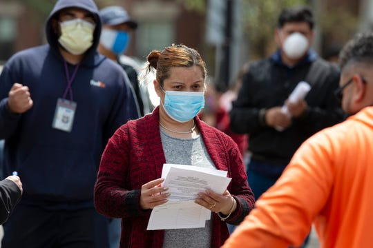 A woman waits to receive food at a distribution site during the coronavirus pandemic, Friday in Chelsea, Mass. (AP Photo/Michael Dwyer)