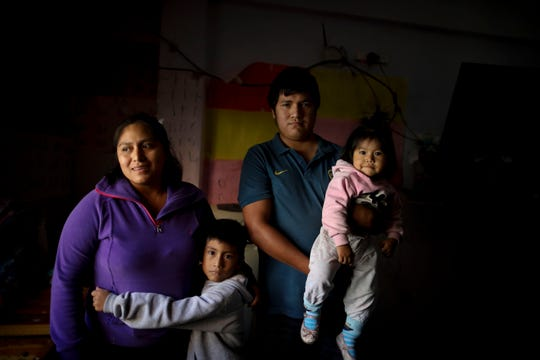 In this April 7, 2020, photo, Rosemary Paez Carabajal, left, her husband Yonoma Saenz, their children Laisa and Leonardo pose for a photo at the room they rent in Buenos Aires, Argentina.