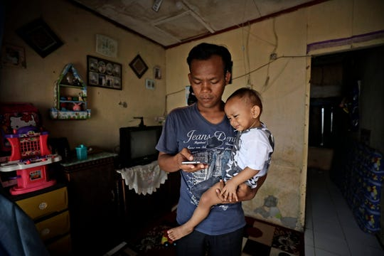 In this Monday, April 20, 2020, photo, Budi Santosa, who was a cook at a Chinese restaurant before losing his job amid the coronavirus outbreak, checks his phone as he carries his young son in his rented house in Jakarta, Indonesia.