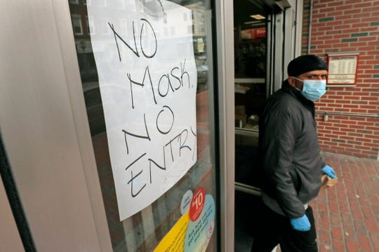 A masked shopper walks past a sign taped to the front door of a CVS Pharmacy, requesting patrons wear masks if they intend on shopping inside due to the COVID-19 virus outbreak, in Chelsea, Mass., April 28, 2020.