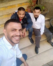 Father of four Hany Hassan, at right, and his friends take a 'selfie' outside the coffee shop where he works, in Cairo, Egypt.