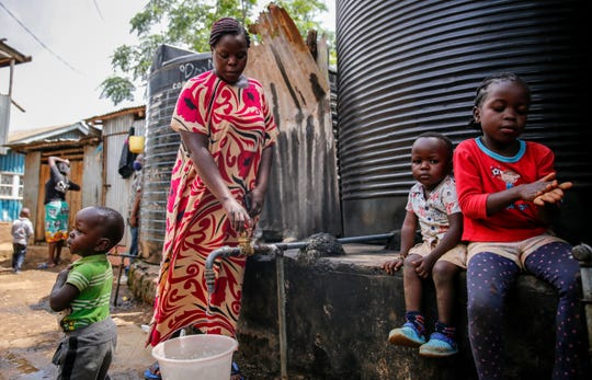 In this April 10, 2020, photo, Judith Andeka a widow and mother of five, fetches water with a bucket in the Kibera slum, or informal settlement, of Nairobi, Kenya.