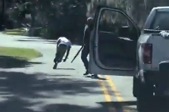 This image from video posted on Twitter Tuesday, May 5, 2020, purports to show Ahmaud Arbery stumbling and falling to the ground after being shot as Travis McMichael stands by holding a shotgun in a neighborhood outside Brunswick, Ga., on Feb. 23, 2020. The AP has not been able to verify the source of the video.