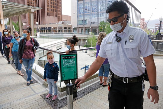 """A security guard, right, adjusts a """"Social Distance"""" sign as people line up outside the Disney store at City Creek Center in Salt Lake City on May 6, 2020."""