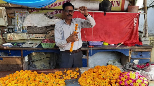Mahesh Verma strings marigold garlands at his flower stall outside a Hindu temple honoring the monkey god Hanuman in Lucknow, India, Friday, May 8, 2020.
