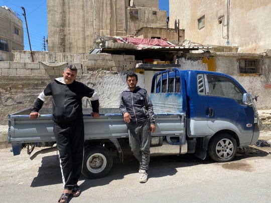 In this April 13, 2020, photo, brothers Mohammed and Khalil Yousef pose in front of a pickup truck in the Palestinian refugee camp of al-Wehdat in Jordan's capital of Amman.