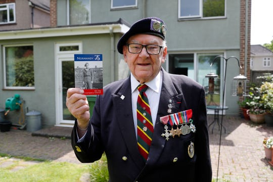 World War II veteran Ken Hay poses in front of his house with a picture of himself in uniform in London, Monday, May 4, 2020.