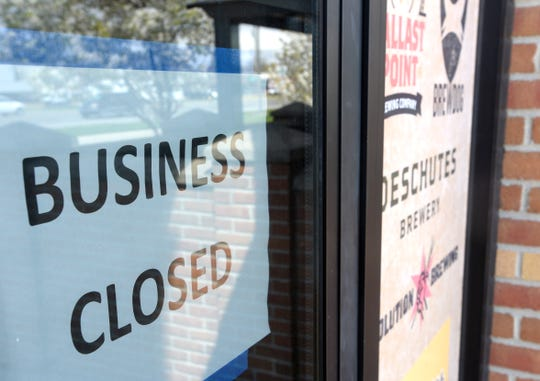 A Business Closed sign is displayed on the front door with business for sale signs out front of the Wintergarden Tavern on Gratiot in Chesterfield Twp., Friday afternoon, May 8, 2020.