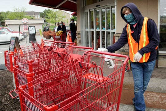 Dilon Moore disinfects shopping carts and controls the number of customers allowed to shop at one time at a Trader Joe's supermarket in Omaha, Neb., Thursday.