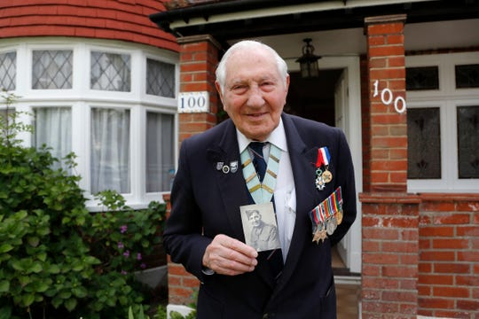 World War II Veteran Mervyn Kersh poses in front of his house with a picture of himself in uniform in London, Monday, May 4, 2020.