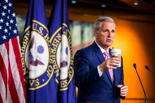 House Minority Leader Kevin McCarthy of Calif. shows his cup of coffee to emphasize that Starbucks is open during a news conference on Capitol Hill, Thursday, May 7, 2020, in Washington.