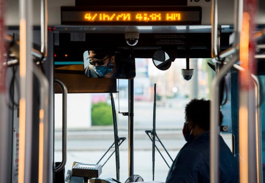 Veteran METS bus driver Robert Crawford is reflected in a rearview mirror, left, as rider Andrico Robinson, right, waits to transfer at Lawndale Commons Shopping Center Thursday morning, April 16, 2020.