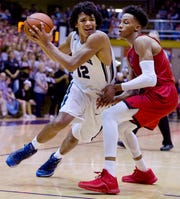 Reitz's Dru Smith (12) drives around New Albany's Romeo Langford to score during their 4A Regional championship game at Seymour High School Saturday night, March 12, 2016.