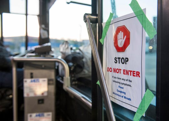 """A sign on the door of every METS bus warning riders to not enter if they have been showing symptoms of illness. The amount of riders allowed on the bus has been reduced to nine due to Indiana's """"Stay-at-Home"""" executive order from Gov. Eric Holcomb to help stop the spread of COVID-19."""