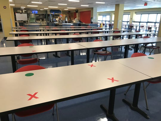 Cafeteria with only one chair to a table and markers indicating where not to sit