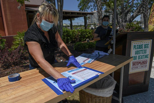 """Erin Parker, general manager of Taco Mundo Kitchen Y Cantina places """"Do Your Part"""" signs for customers to read about the coronavirus at the front of the restaurant in North Myrtle Beach, South Carolina Thursday, May 7, 2020."""