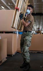 U.S. Navy Culinary Specialist Seaman Kenneth Baily, from Houston, moves a pallet during mail call aboard the aircraft carrier USS Theodore Roosevelt May 6. The carrier's COVID-negative crew returned from quarantine beginning on April 29 and is making preparations to return to sea to continue their scheduled deployment to the Indo-Pacific.