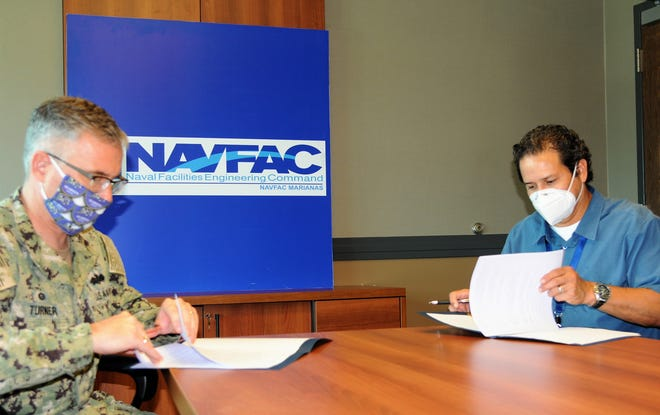 NAVFAC Marianas Commanding Officer Capt. Daniel Turner, left, and GWA General Manager Miguel Bordallo sign a memorandum of understanding to share information and data related to Guam's water and wastewater systems May 8.