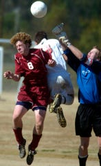 Henderson County's Jared Silverthorn, left, goes up against Daviess County's Wesley Hayden (center) and goalie Clay Kirn to head the ball near the Daviess County goal in the 2006 Third Region soccer final Deer Park Elementary School in Owensboro on Oct. 21, 2006.